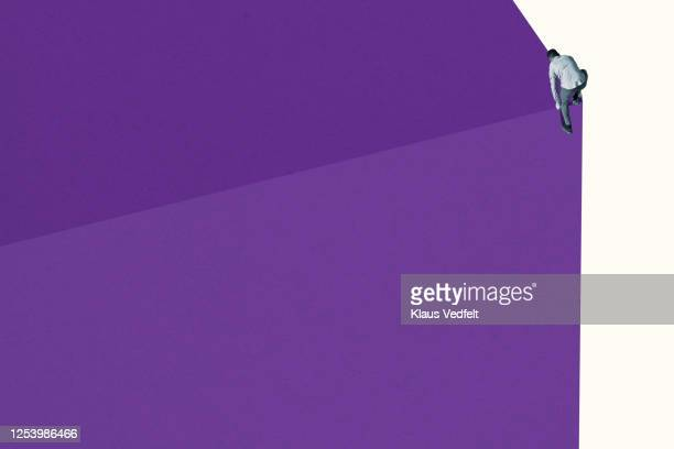 young man climbing on purple wall - oresund region stock pictures, royalty-free photos & images