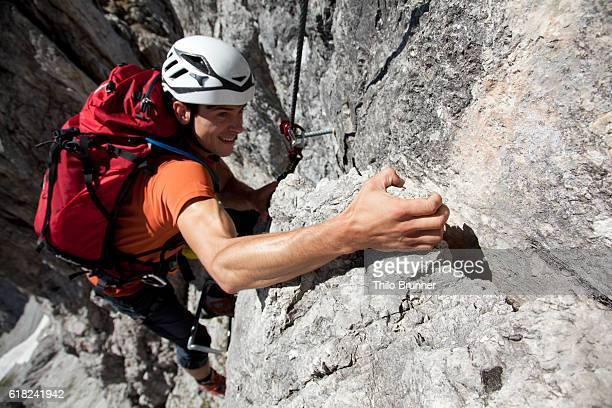 Young man climbing on rock in high mountains