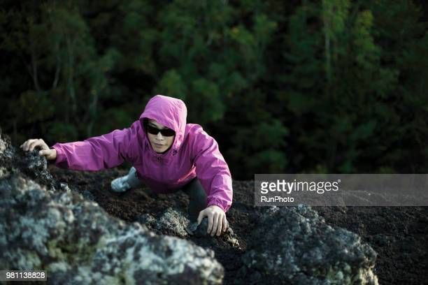 young man climbing on rock - satoyama scenery stock pictures, royalty-free photos & images