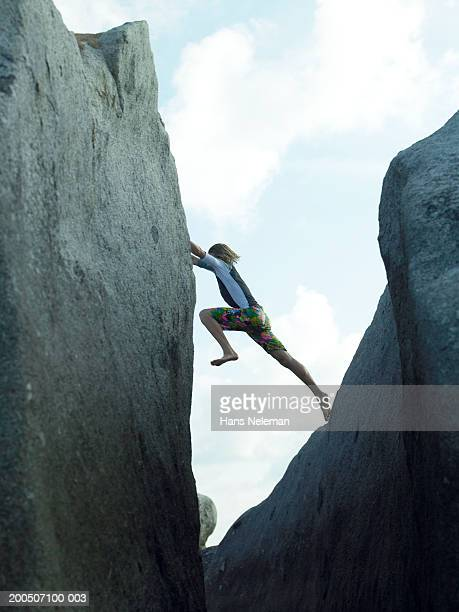 Young man climbing rocks by sea, side view