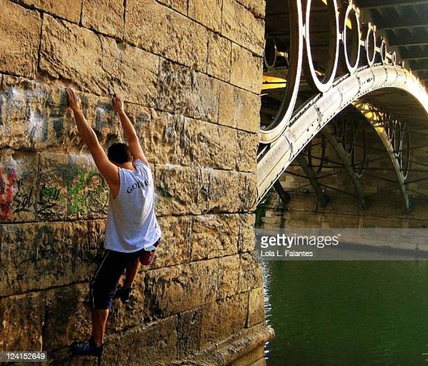 Young man climbing Triana bridge's wall
