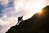 Young man climbing up a mountain.