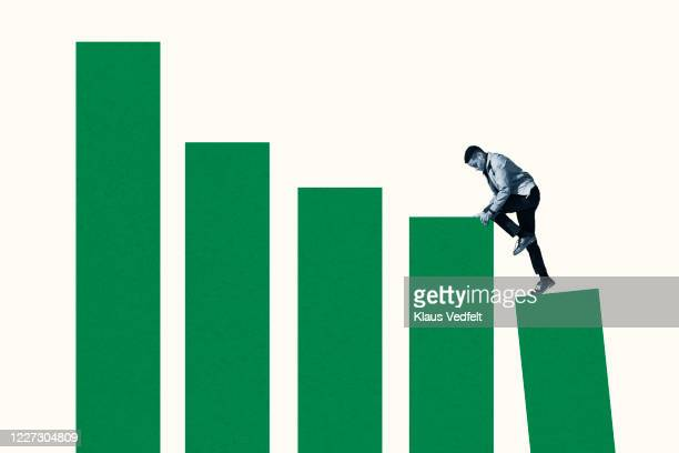 young man climbing up on green bar graphs - social issues stock pictures, royalty-free photos & images