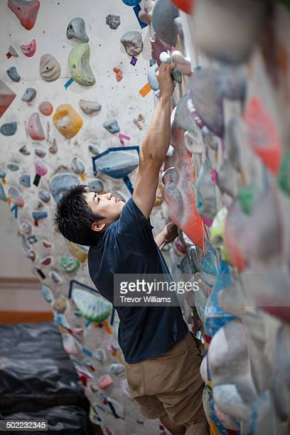 A young man climbs at a bouldering gym.