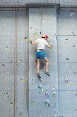 Young man climbs indoor rock wall