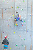 Young man climbs indoor rock wall