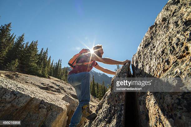 Young man climbs steep rock, moving up