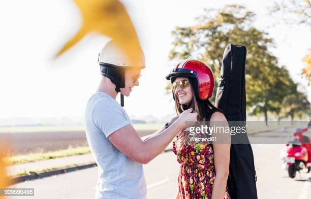 Young man closing helmet of girlfriend with motor scooter in background