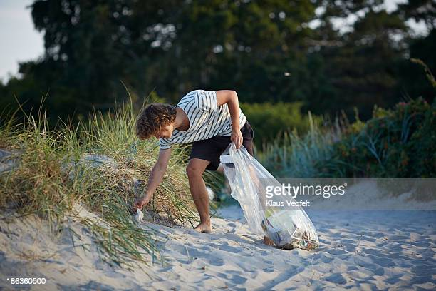 young man collecting trash on beach - levantando - fotografias e filmes do acervo
