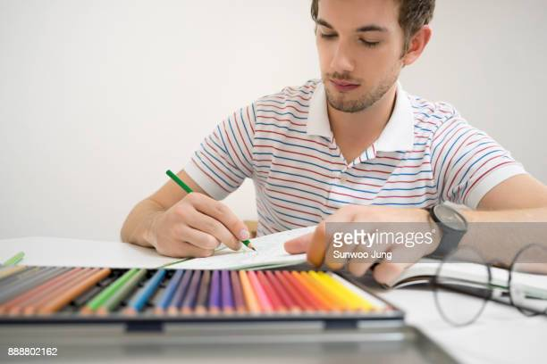 young man coloring an adult coloring book - colouring stock photos and pictures