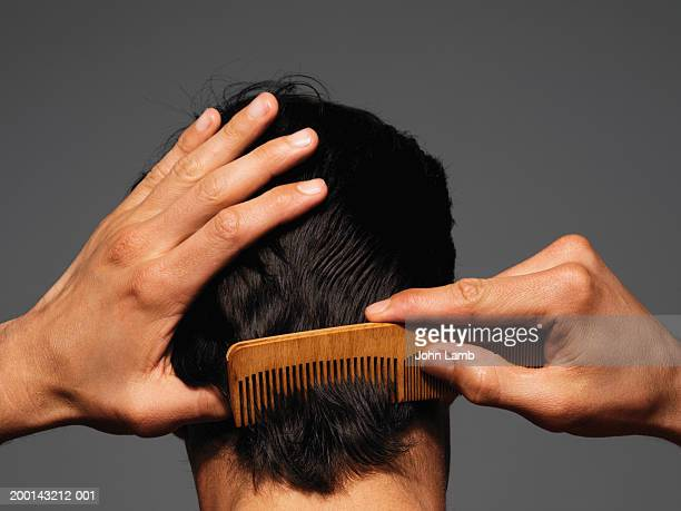 young man combing back of head, rear view - penteando imagens e fotografias de stock