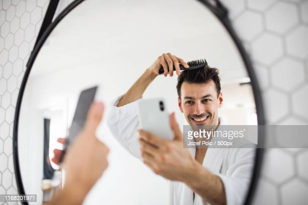 young man combing hair in the bathroom in the morning, taking selfie - penteando imagens e fotografias de stock