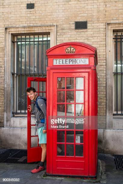 young man comes out of red phone booth, london, england, great britain - telephone box stock pictures, royalty-free photos & images