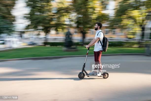 彼の電子スクーターで通勤する若い男 - %e... ストックフォトと画像