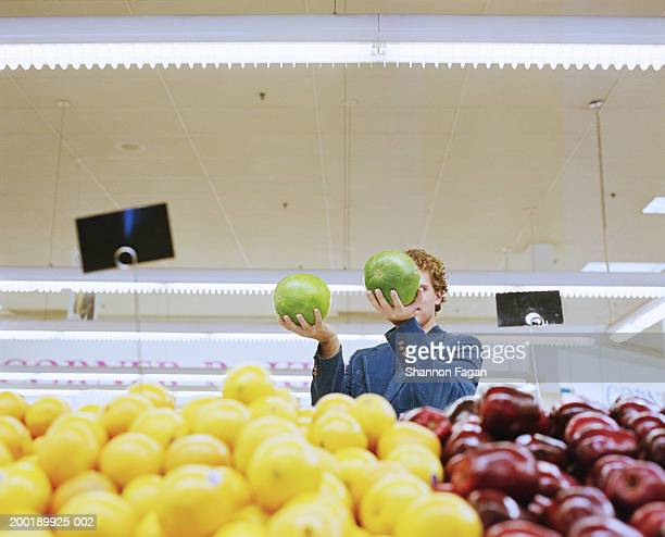 Young man comparing two watermelons in supermarket, low angle view