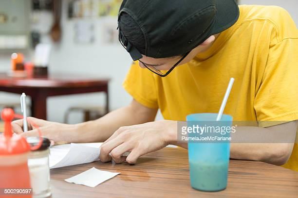 Junger Mann Sie Papierkram in einem Café