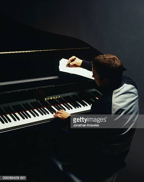 Young man composing music at grand piano, rear view