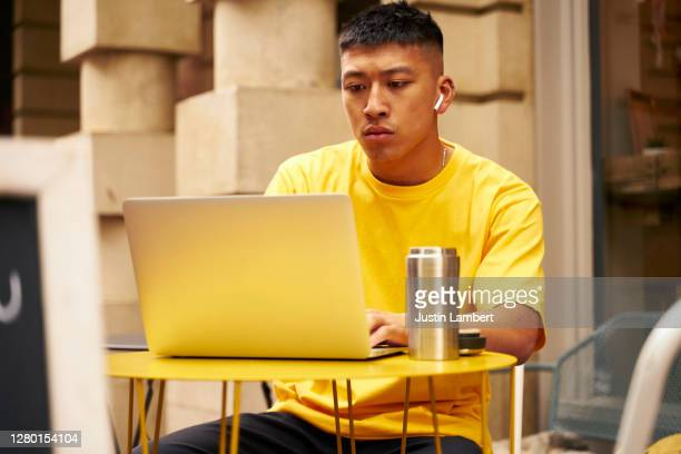 young man concentrating working at his laptop outside a cafe - using laptop stock pictures, royalty-free photos & images