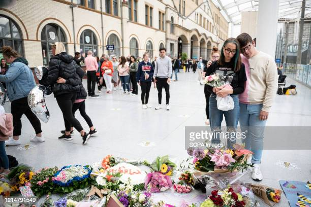A young man consoles his friend in front of the floral memorial created at Victoria station during the commemoration People gather at Victoria...