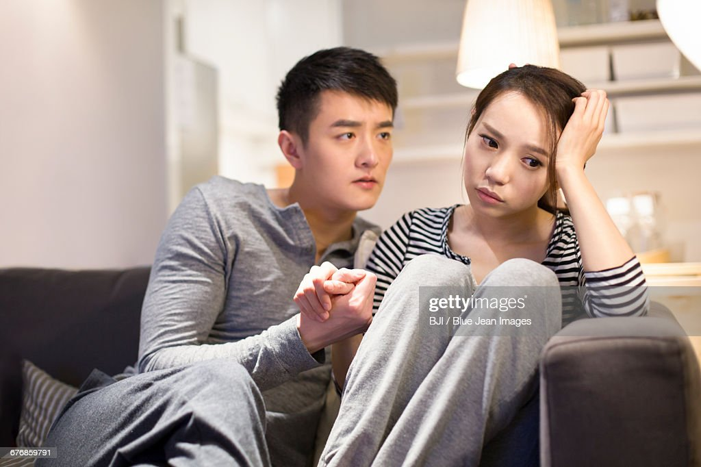 Young man consoling his sad girlfriend on living room sofa : Stock Photo