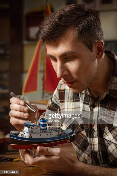 young man constructing a ship model - model building stock photos and pictures