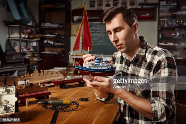 Young man constructing a ship model