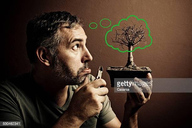 jeune homme sur sa mort de bonsaï envisagent - jardinier humour photos et images de collection