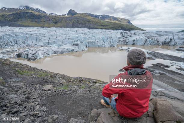 Young man contemplating glacier lake in Iceland