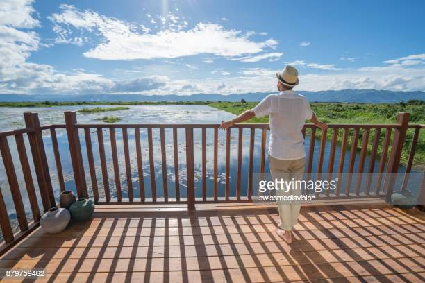 young man contemplating lake view from balcony, myanmar - expatriate stock pictures, royalty-free photos & images