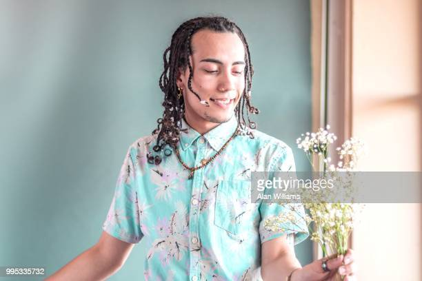Young man contemplating native flower