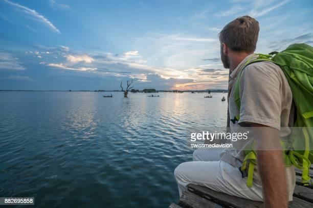 若者は Ubein 橋、ミャンマー、アジアから熟考サンセット