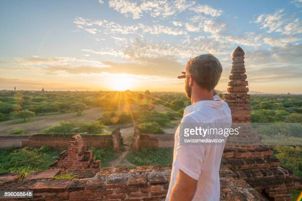 young man contemplating the bagan archeological zone at sunrise, burma - unesco world heritage site stock pictures, royalty-free photos & images