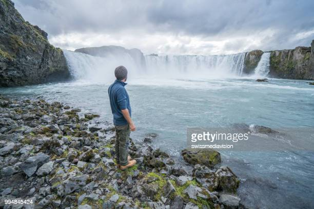 Young man contemplating waterfall in Iceland