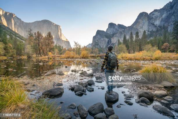 young man contemplating yosemite valley from the river, reflections on water surface - yosemite nationalpark imagens e fotografias de stock