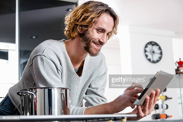 young man cooking and checking recipe on tablet