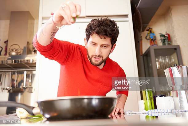 young man cooking at home - season stock pictures, royalty-free photos & images