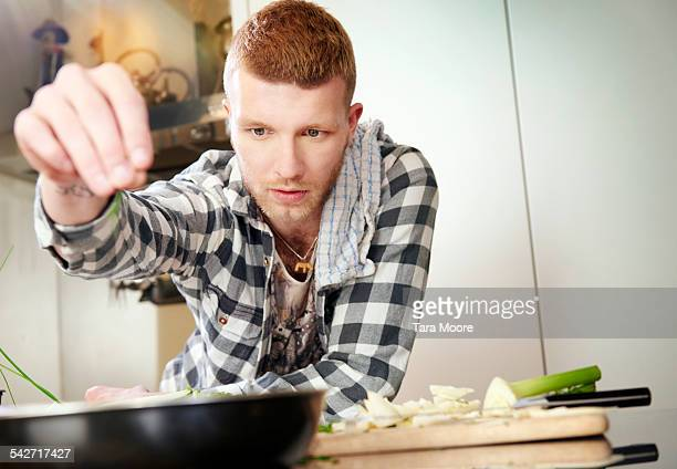 young man cooking at home - ein mann allein stock-fotos und bilder