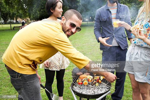 A young man cooking burgers on a BBQ in summer