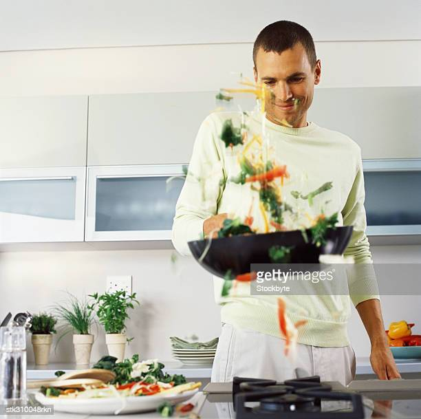 young man cooking food in the kitchen
