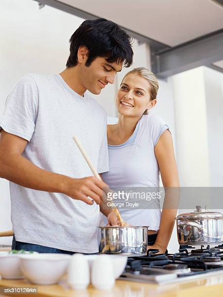 young man cooking food with a young woman standing beside him - hob stock photos and pictures
