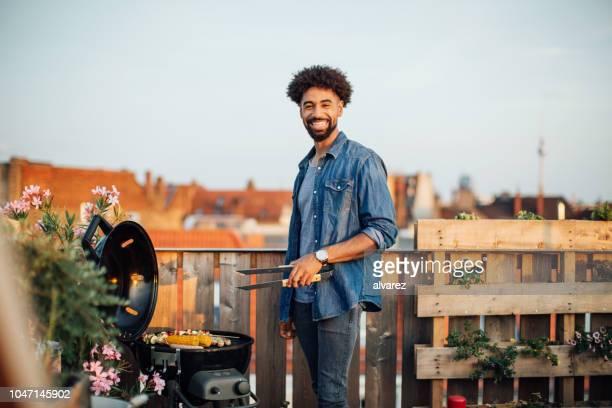junger mann kochen auf grill party auf dem dach - grillen stock-fotos und bilder