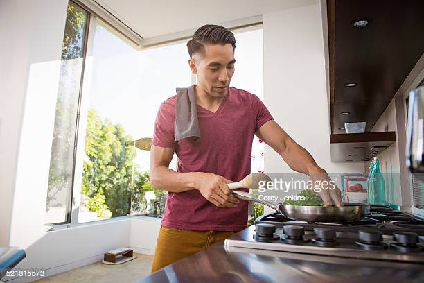 young man cooking on hob in kitchen - burner stove top stock pictures, royalty-free photos & images