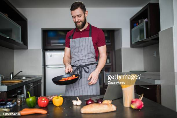 young man cooking vegetables with a pan - cibo pronto foto e immagini stock