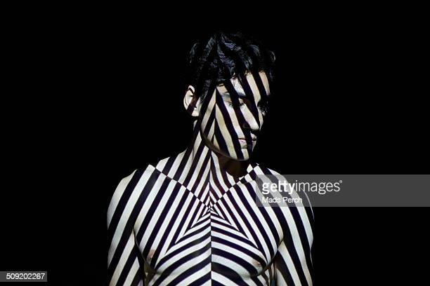 young man covered by abstract patterns of light - black and white stock pictures, royalty-free photos & images