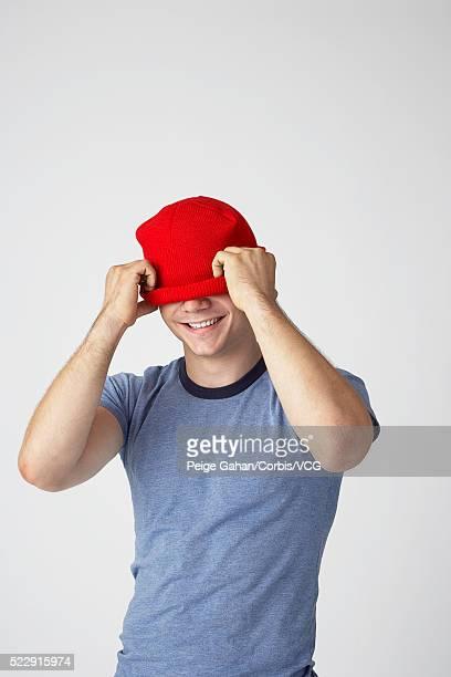young man covering eyes with red ball cap - augen zuhalten stock-fotos und bilder