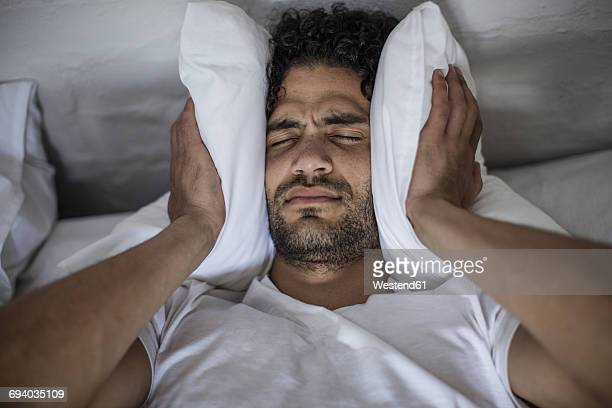 young man covering his ears with a pillow - noise stock pictures, royalty-free photos & images