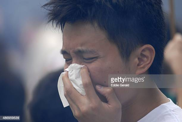 A young man covering his face due to air pollution in Beijing China