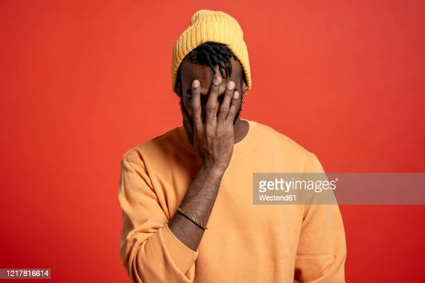 young man covering his face in front of orange wall - head in hands stock pictures, royalty-free photos & images