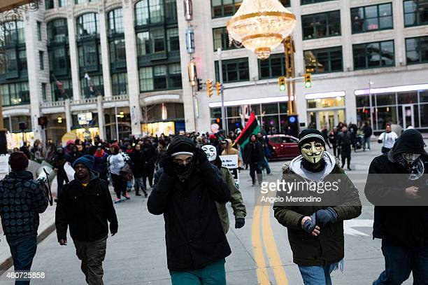 A young man covers his face with a mask as demonstrators march to protest police violence on E14th Street December 20 in Cleveland Ohio