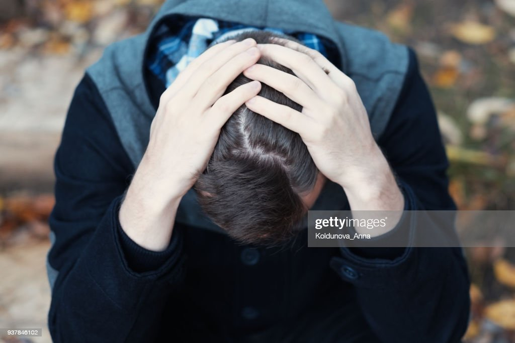 Young man covers his face with his hands in grief : Stock Photo